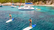 Catamaran Anchoring and People Stand Up Paddling Corfu Island